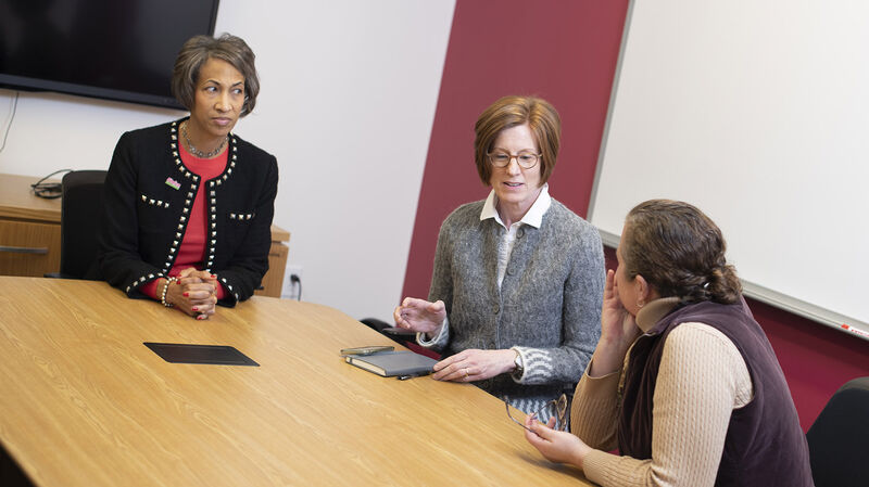 Three Foundation staff having a conversation around a conference table