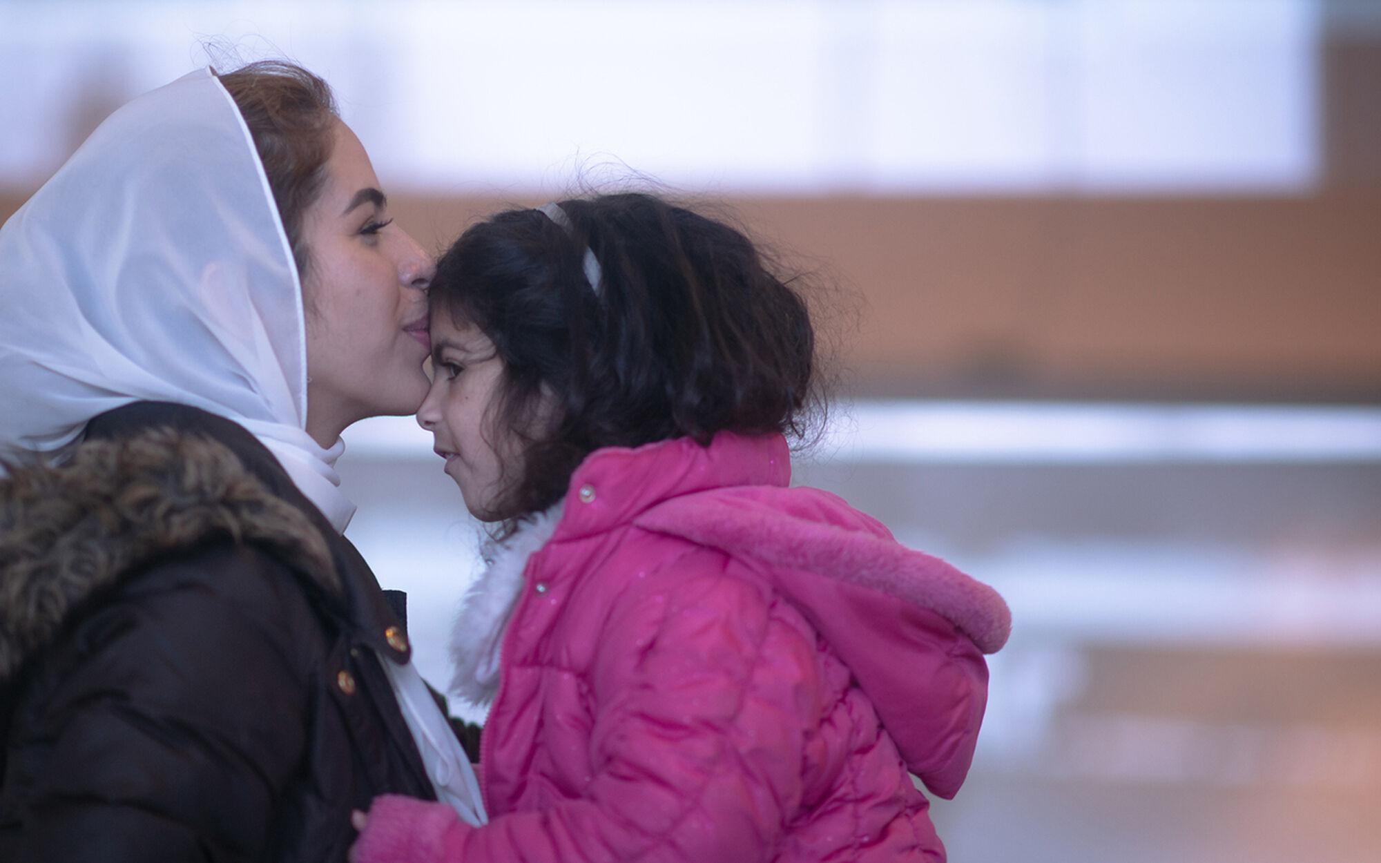 Refugee mom and daughter at airport
