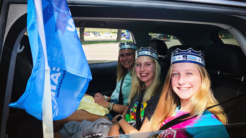 Three girls wearing State Fair crowns while sitting in a vehicle during the State Fair Food Parade