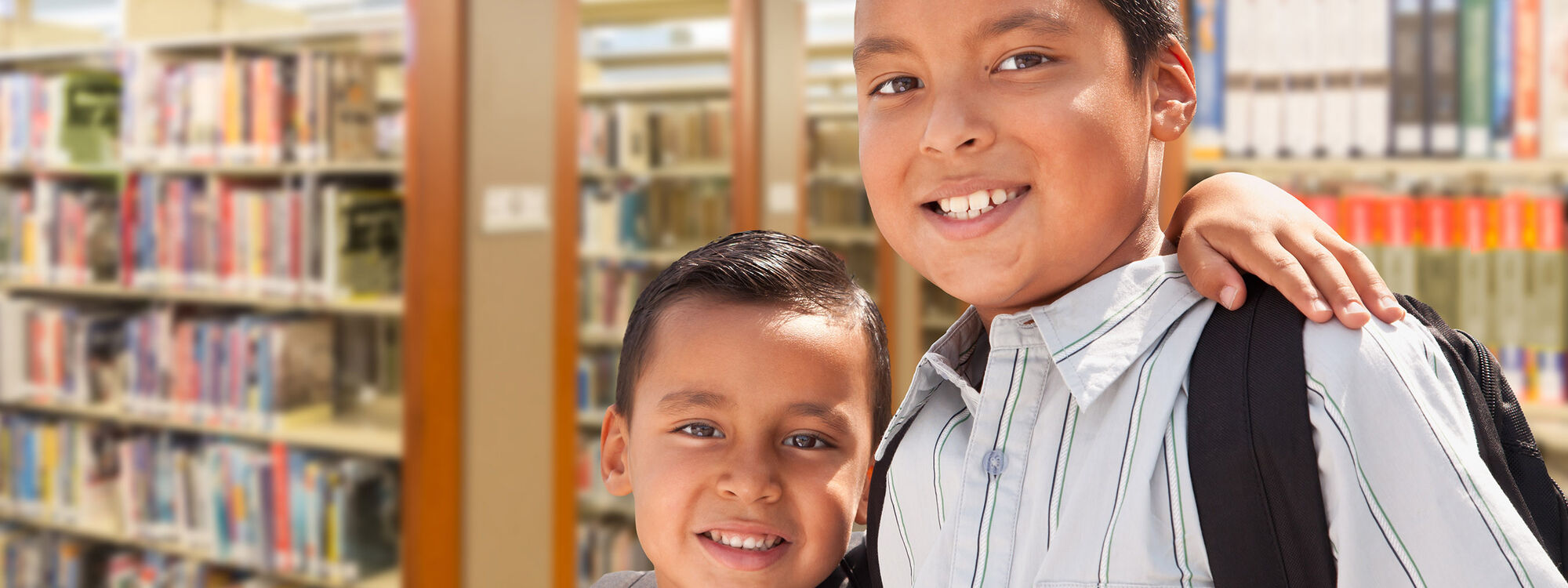 Green Card Voices - two children wearing backpacks in a library