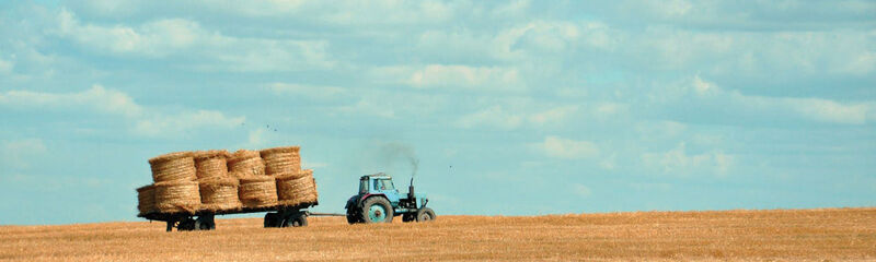 Tractor and hay bales in a field